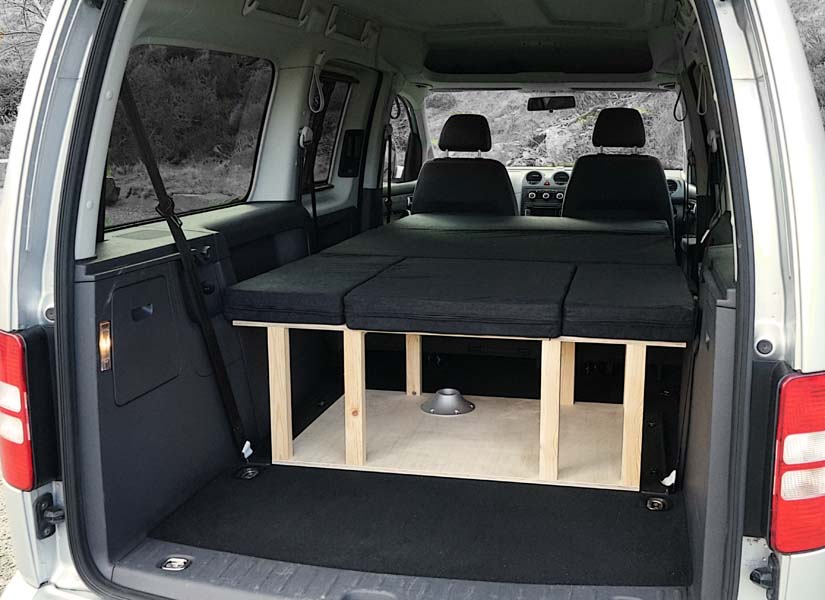 The VW Caddy Maxi Life camper van conversion in sleeping mode with the optional cushion set.